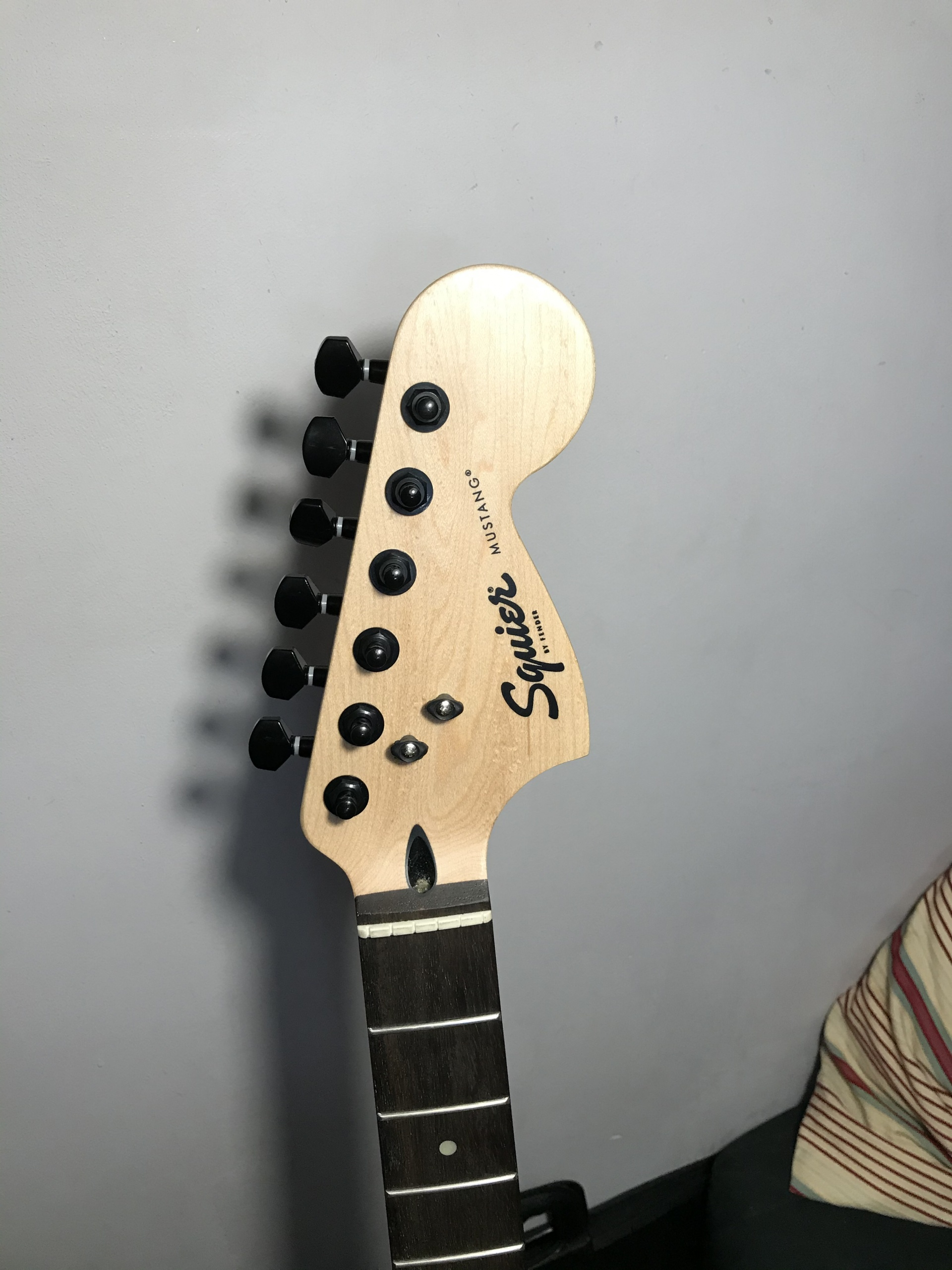 Squier Bullet Mustang - headstock with black locking tuners and graphtech string trees